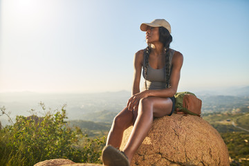 fit female hiker resting on top of mountain with view of san diego behind her
