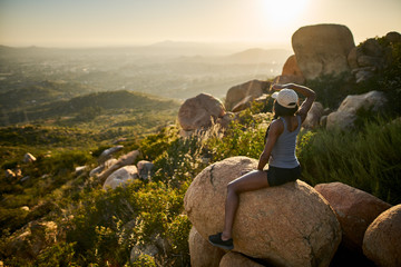 fit female hiker sitting on rock at mountain top relaxing