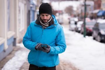 Man using mobile phone while walking on sidewalk
