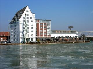 Eisschollen vor sanierten alten Lagerhäusern auf dem Dortmund-Ems-Kanal am alten Hafen von Münster in Westfalen im Münsterland bei Frost und Minusgraden vor blauem Himmel