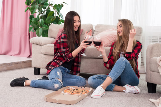 Time to relax! Two smart stylish girls   dressed in blue scruffy jeans with red plaid shirts clinking glasses with wine for a toast while sitting on the carpet at home.