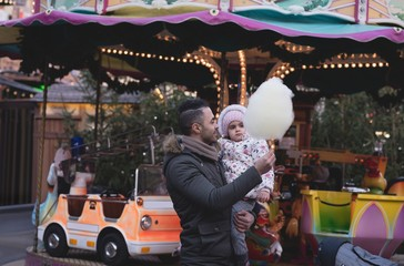 Father and daughter having cotton candy at dusk