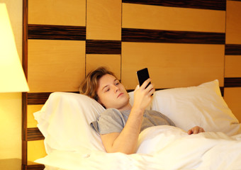 young man relaxing on her bed,using smartphone