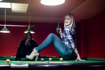Attractive blond is sitting on billiard table
