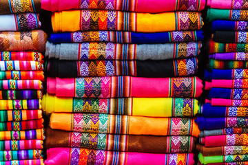 Close-up of colorful blankets stacked with Andean designs