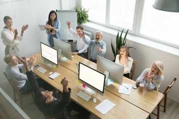 Excited diverse team celebrating corporate business success applauding african coworker congratulating happy black colleague with achievement, good result, victory in coworking office, top view