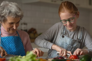 Grandmother and granddaughter cutting vegetables in kitchen