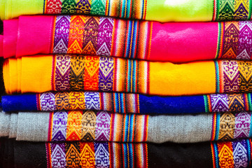 Macro close-up of colorful blankets stacked with Andean designs