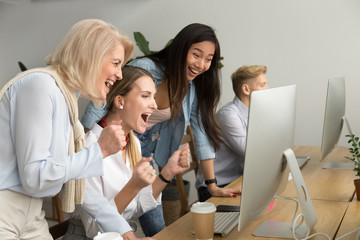 Diverse young and senior female colleagues excited by online win or business achievement, multiracial happy businesswomen celebrating victory looking at computer screen watching cheering winning team