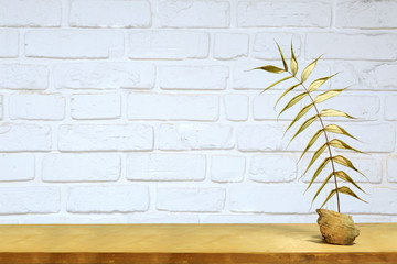 Złoty liść na półce na tle białej ścianie z cegły.