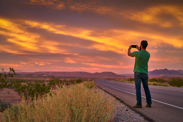 man using smartphone to take photo of colorful sunset beside nevada road in desert