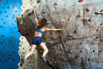 Sportswoman in shorts ascending artificial wall.