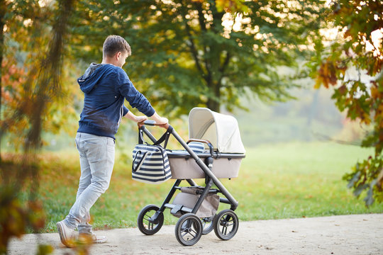 Man with baby stroller walks in the autumn park at sunset