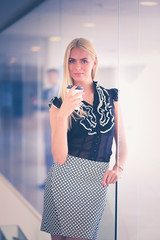 Businesswoman holding a cup of coffee standing in office .