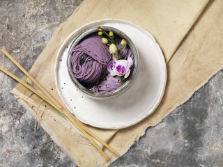 Lavender noodle with orchid flower garnish in stone bowl