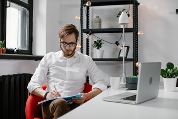 Office worker with notepad at computer