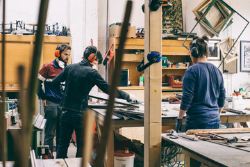 Three Young Carpenters Working Together in Bright Workshop