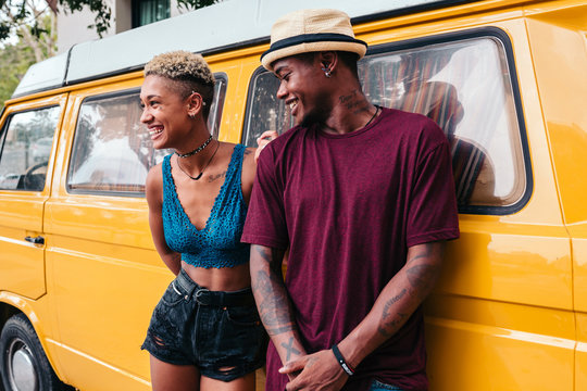 Mixed race couple with a yellow camper van