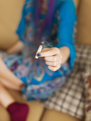 Unrecognizable woman showing cigarette with weed