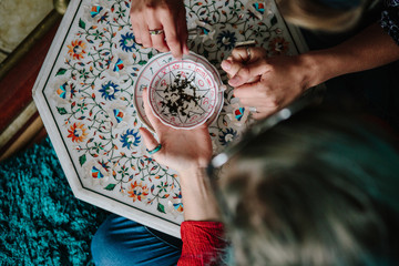 Tea leaf consultation, a fortune teller reading tea leaves