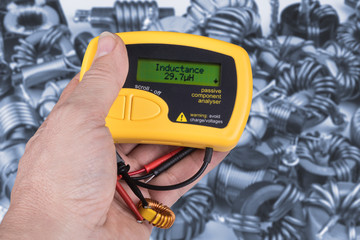 Detail of hand with digital meter of electric passive components. Technical expert when testing inductance of coils using the measuring instrument. Idea of professional work in electronics industry.