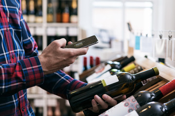 Wine: Man Uses Cell Phone To Research Bottle Of Wine