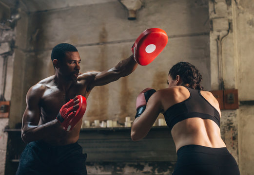 Strong brunette woman boxing indoors with his coach.