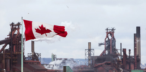 A Canadian flag flies above another industry site with ArcelorMittal Dofasco in the background in Hamilton