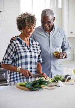 Senior African American couple chopping vegetables together in the kitchen