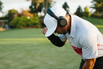 close up of a man listening to headphones as he is about to putt on a golf course
