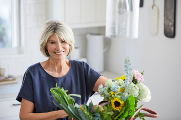 Senior woman in kitchen with farmers market basket with vegetables and flowers