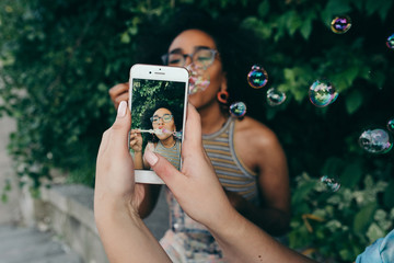 Two young friends blowing bubbles and taking pictures