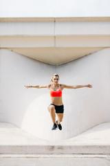 Beautiful sportswoman in motion of jump