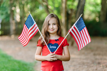 Beautiful young girl holding two flags of the united states