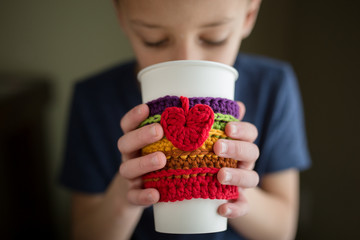 Boy drinking from disposable cup with crocheted rainbow cup sleeve