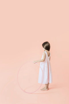 Girl with hula hoop on pink background