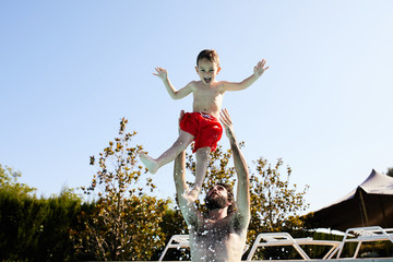 Man throwing up son in swimming pool