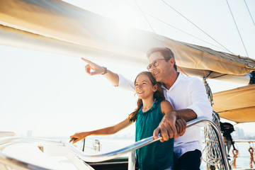 Father and daughter enjoying a sunny day on a sailboat.