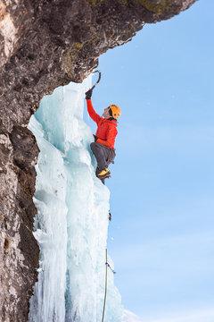 Man ice climbing on frozen waterfall using ice axes