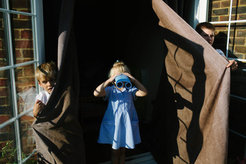 Three children perform a play in which a small girl sees far off lands through her (cardboard) binoculars.