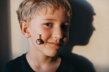 Cute smiling blond boy with snails on his face