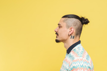 Portrait Of Tattooed Man In Front Of The Yellow Background