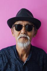Senior asian man portrait on pink background