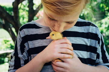 Baby girl kissing a baby duck