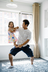 Father and his adorable daughter playing at home
