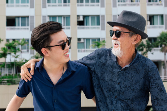 Stylish old man having a casual talk with his son on the rooftop of the building