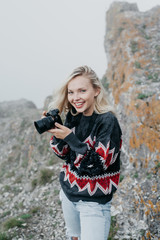Girl in sweater using photo camera