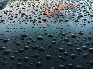 Many Water Drops on blue surface of a car