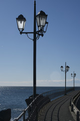 Wrought Iron Lamp Posts Line the Walkway on the Edge of the Sea