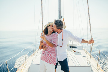 Kissing lovely couple on sailboat.